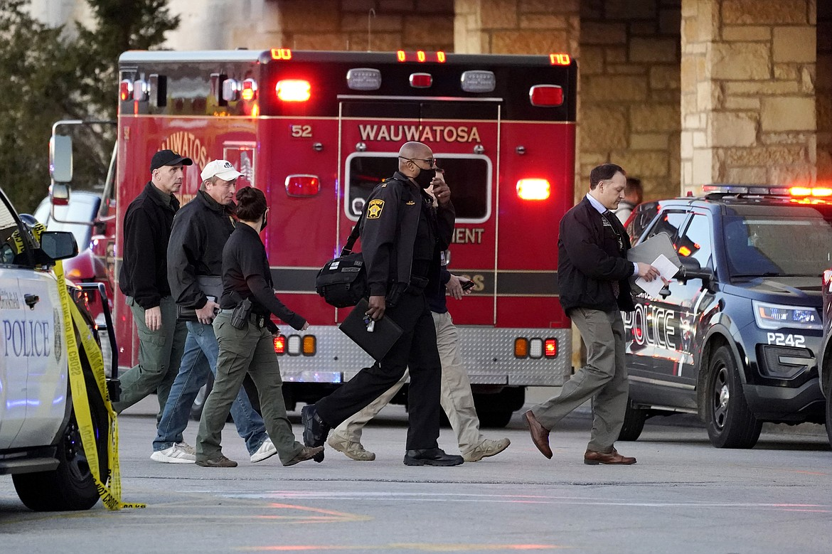 Police officials walk to the Mayfair Mall, Friday, Nov. 20, 2020, in Wauwatosa, Wis. Multiple people were shot Friday afternoon at the mall and police are still searching for the shooter.
