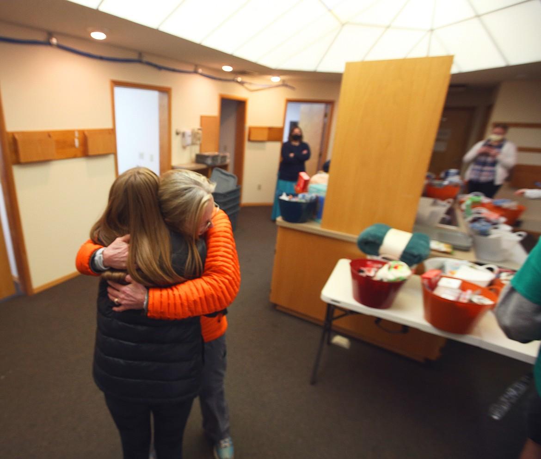 Kootenai Health nurse Sandra Dolyniuk hugs Post Falls High School student Reagan Hartzell as she and classmates delivered gifts to the testing center Friday morning.