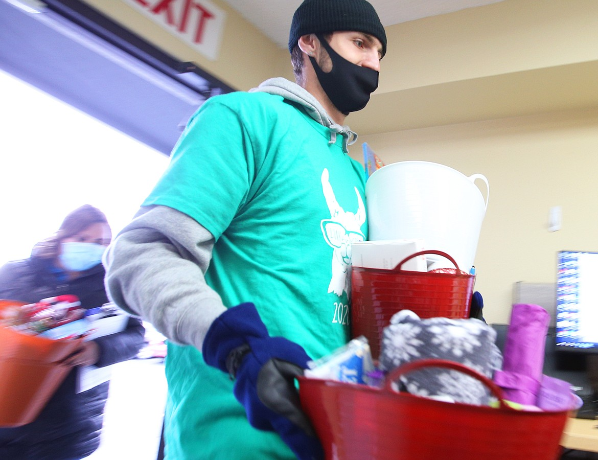 Post Falls High School student Alex Horning carries gifts collected at the school into the coronavirus testing center at Kootenai Health on Friday.