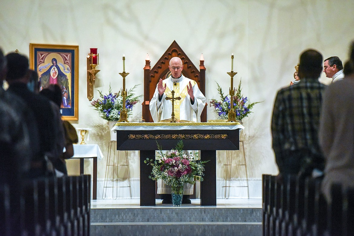 Father Rod Ermatinger reads at the altar during Mass at St. Matthew's Catholic Church in Kalispell on Saturday, Nov. 21. (Casey Kreider/Daily Inter Lake)