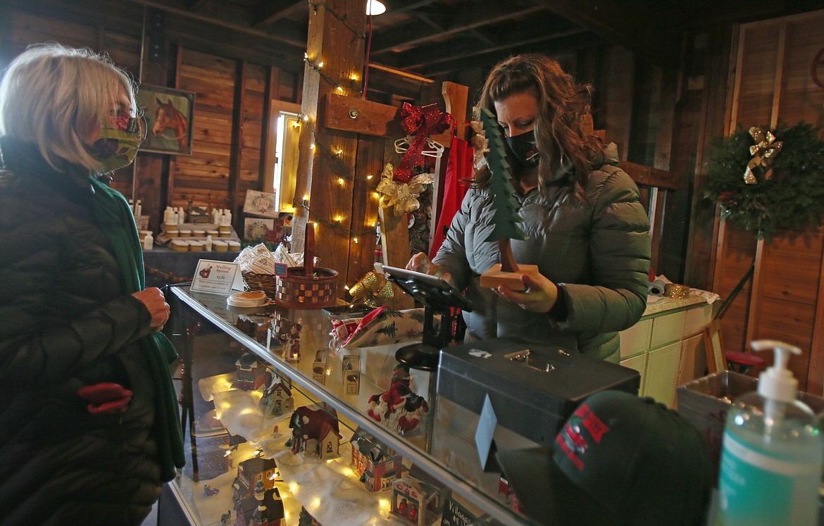 Beth Tysdal, who runs the gift shop at Cable Creek Farm, wraps up a few locally made items for Debbie Morris on Friday. Everything in the gift shop is made by local artisans.