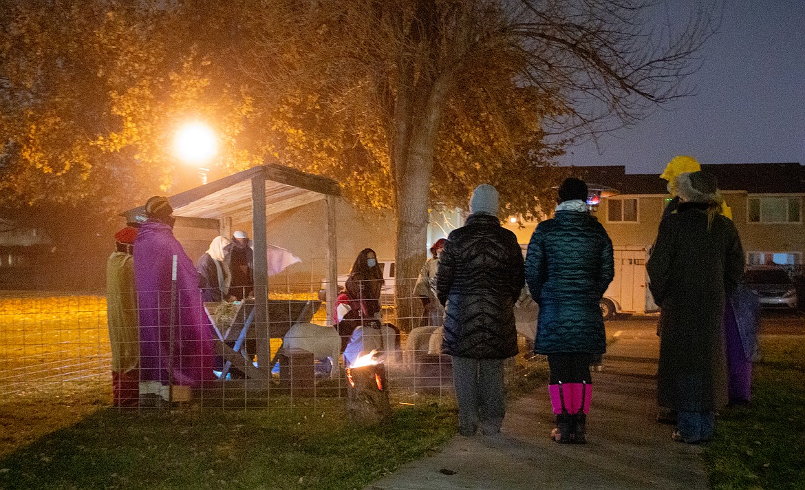 A group stands by listening to the speaker at the final stop of the Living Nativity on Saturday evening, the Nativity Scene, provided by volunteers from the Church of Jesus Christ of Latter-day Saints.