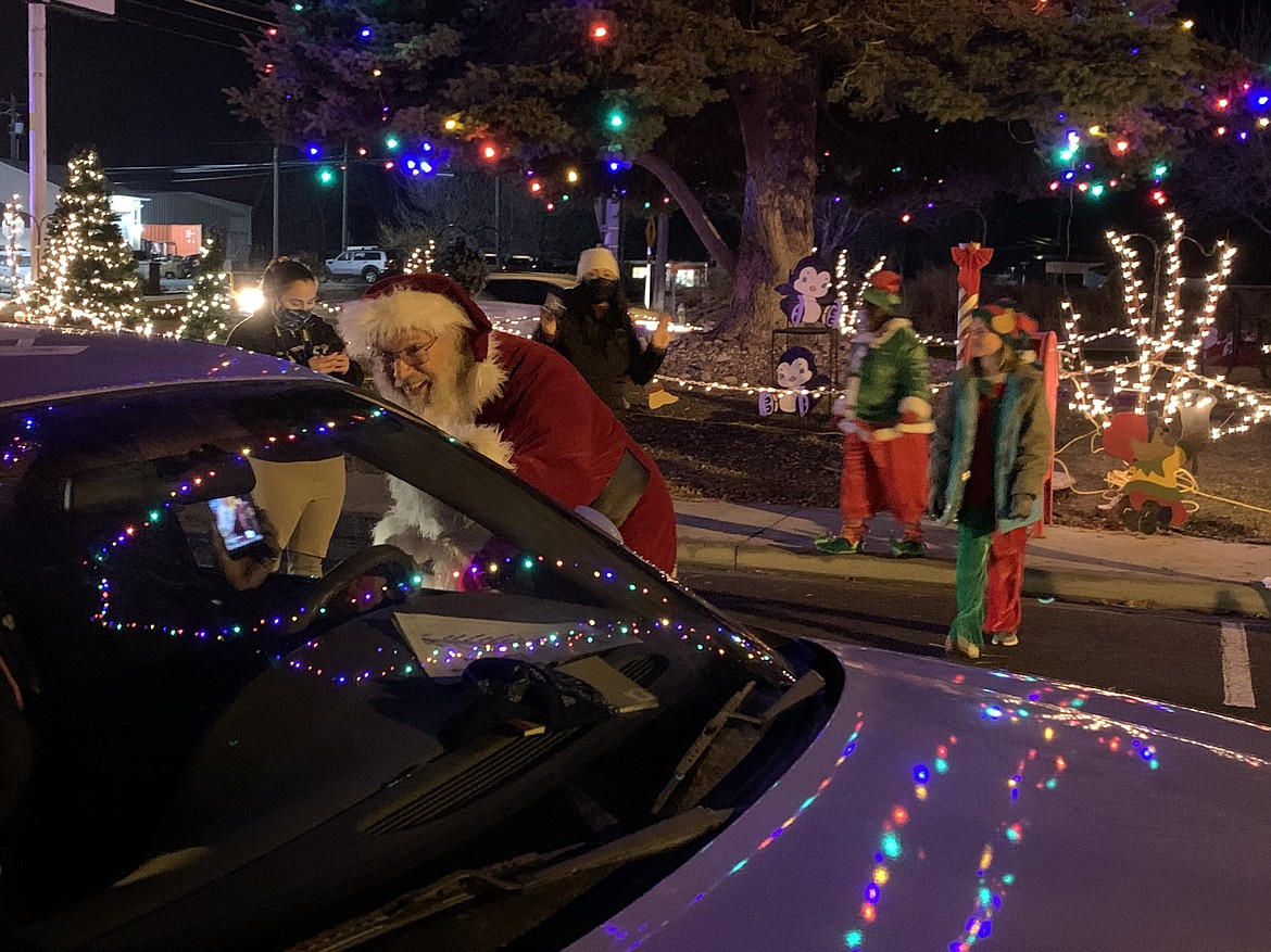 Santa Claus waves and smiles to a family as they swing through the drive-thru lights display in Quincy on Friday night, kicking off the weekend Holiday Celebration.