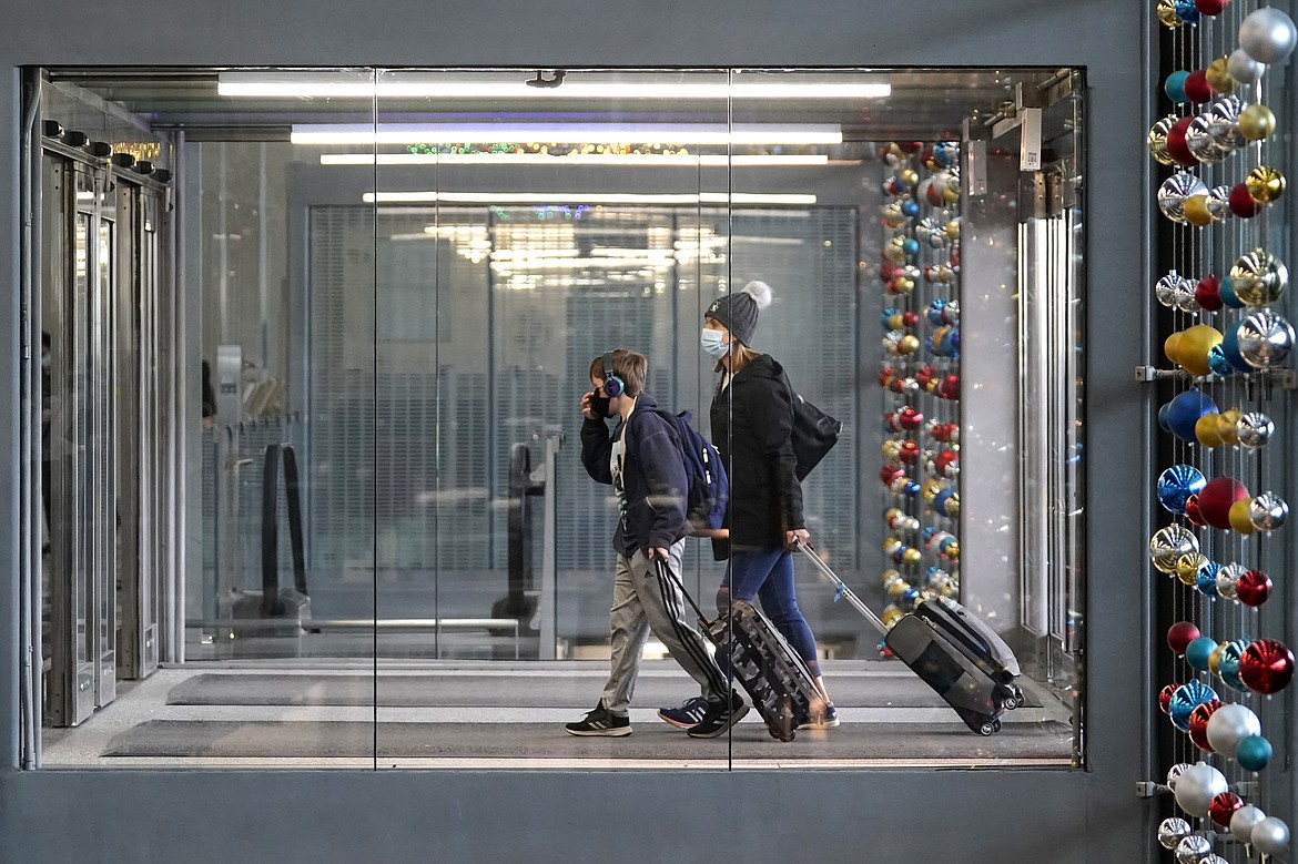 In this Nov. 29, 2020, file photo, travelers walk through Terminal 3 at O'Hare International Airport in Chicago. With some Americans now paying the price for what they did over Thanksgiving, health officials are warning people — begging them, even — not to make the same mistake during the Christmas and New Year's season.