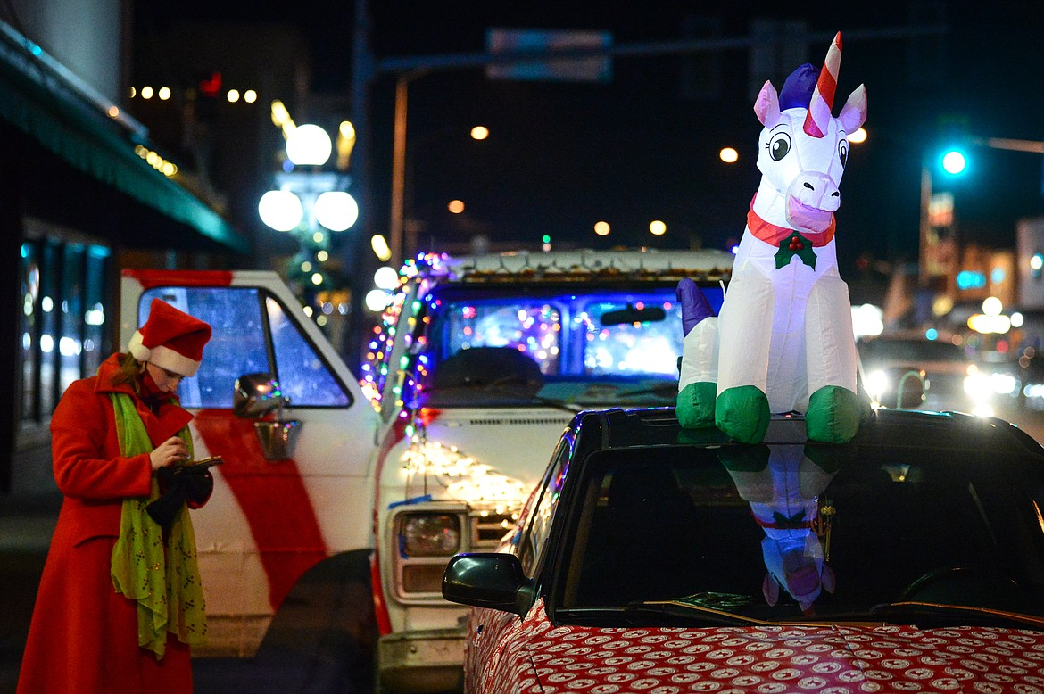 Tiffany Miciewicz, who organized the Elevation Christmas Light Car Show with her husband Trever, stands next to a vehicle with an illuminated unicorn in downtown Kalispell on Saturday, Dec. 12. (Casey Kreider/Daily Inter Lake)
