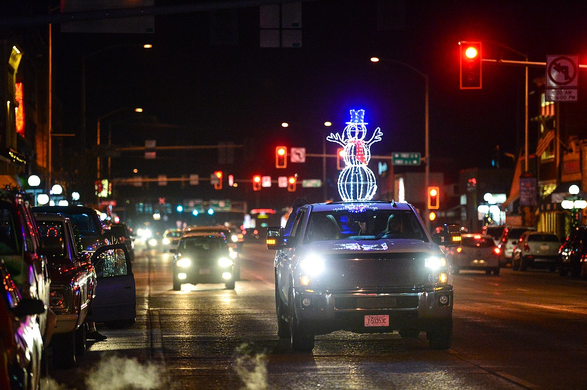 A vehicle with an illuminated snowman cruises down Main Street at the Elevation Christmas Light Car Show in downtown Kalispell on Saturday, Dec. 12. (Casey Kreider/Daily Inter Lake)