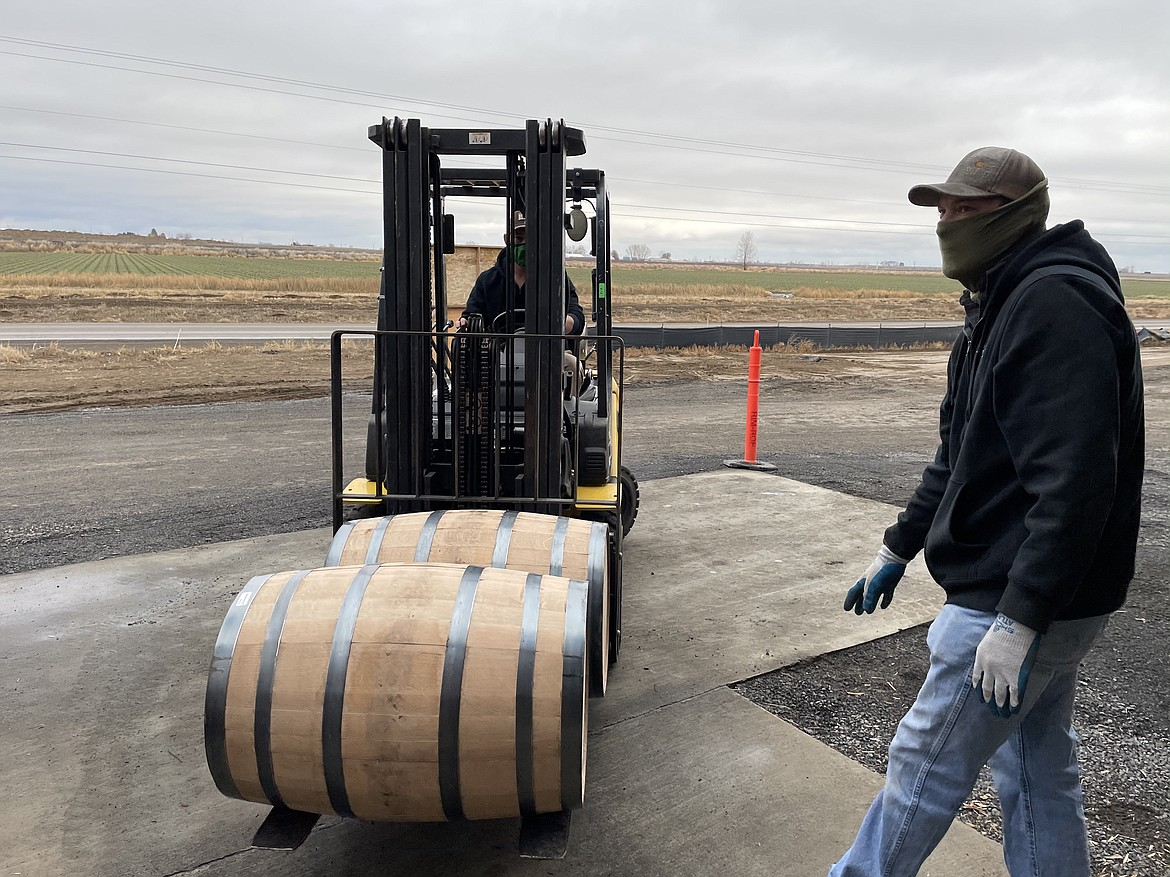 Woodinville Whiskey Co. warehouse workers load barrels of whiskey.