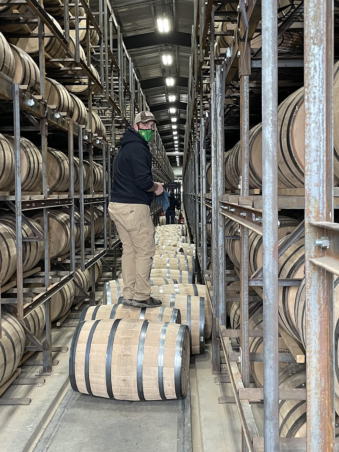 A Woodinville Whiskey Co. warehouse worker stands on a whiskey barrel.