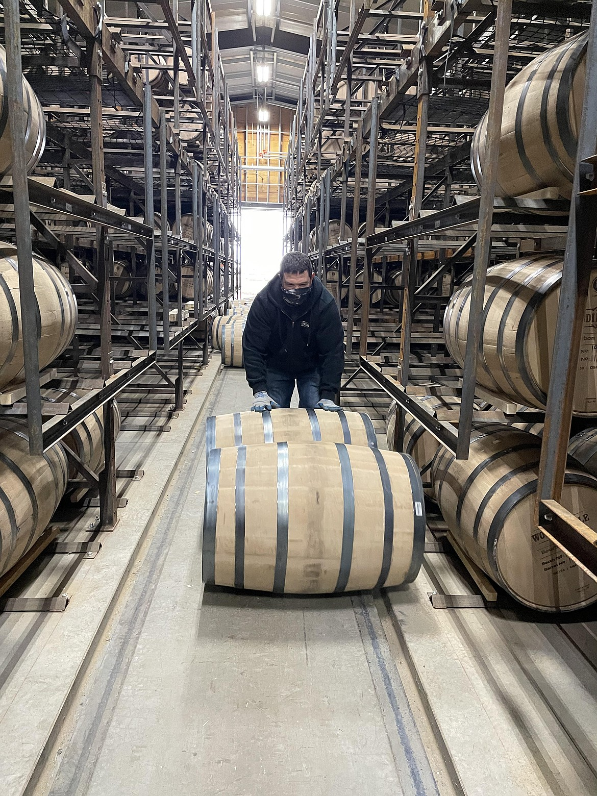 Elijah Gregg rolling barrels at one of Woodinville Whiskey Co.'s Quincy warehouses.