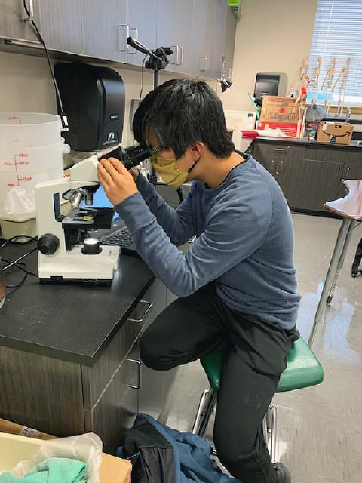 Whitefish High School sophomore Joshua Pitchford uses a microscope as he gets assistance in his biology class on a recent Wednesday. (Photo courtesy of Whitefish School District)