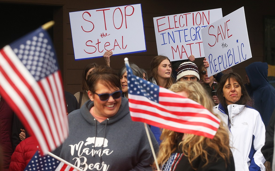 People hold flags and signs at Tuesday's rally in Coeur d'Alene