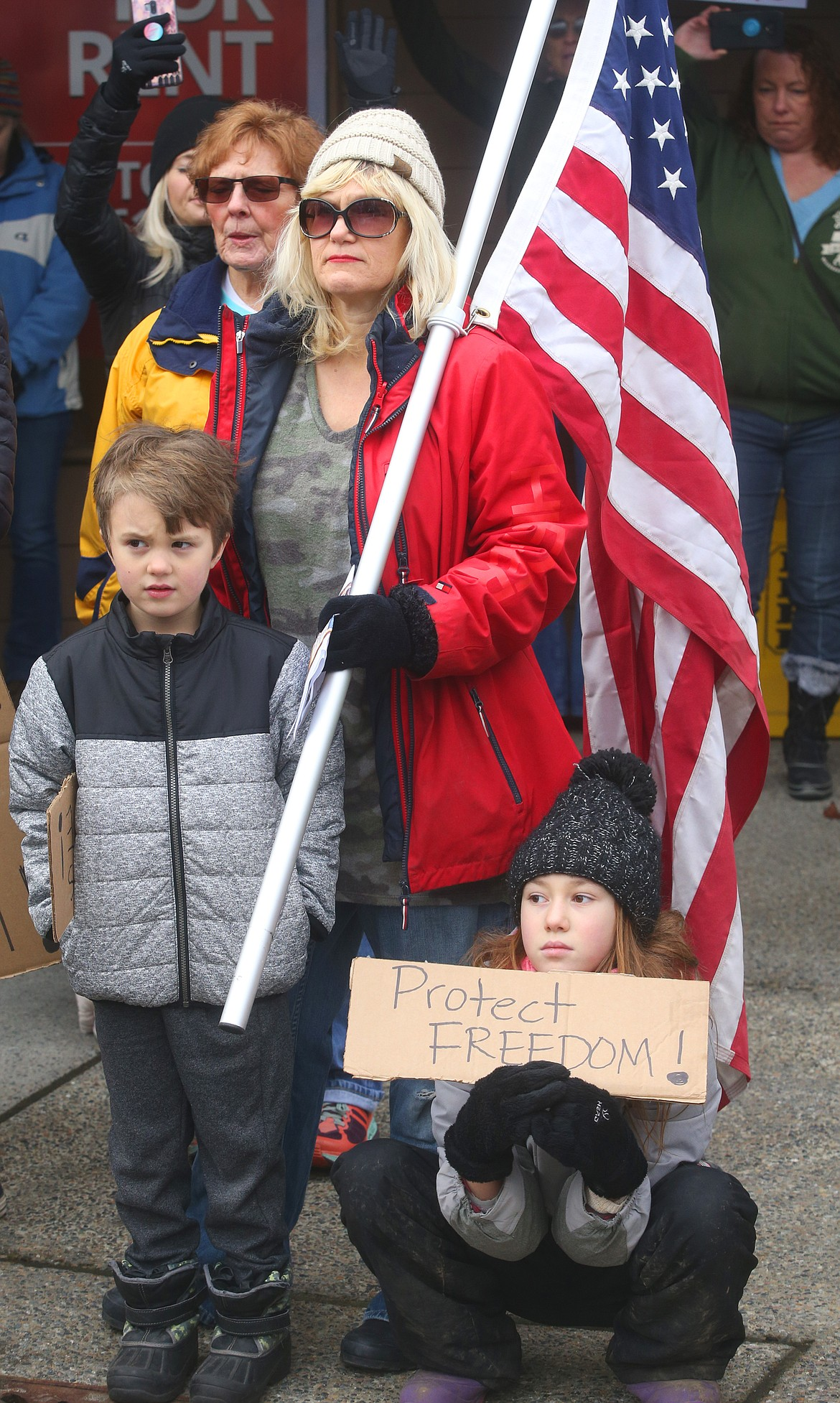 Judy Buessing holds a flag as she stands with two children during a moment of prayer at Tuesday's rally for President Donald Trump.
