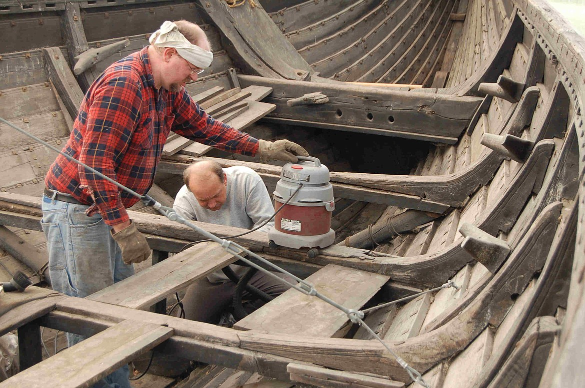 Andrew Woods and David Nordin working on the interior construction of a replica Viking longboat that didn't have benches for the oarsmen, who instead used their own individual chests containing personal possessions to save space.