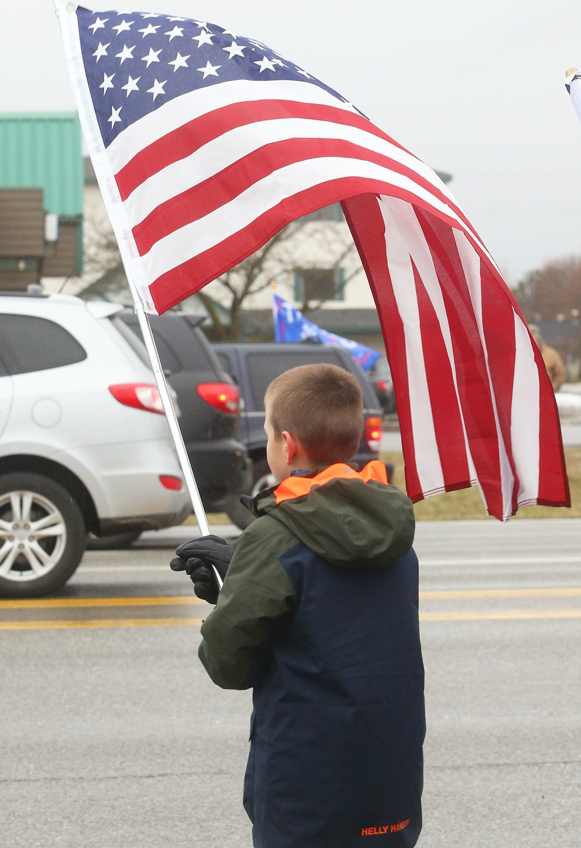 Tyson Schmalz waves a flag as he stands along U.S.95 Wednesday.