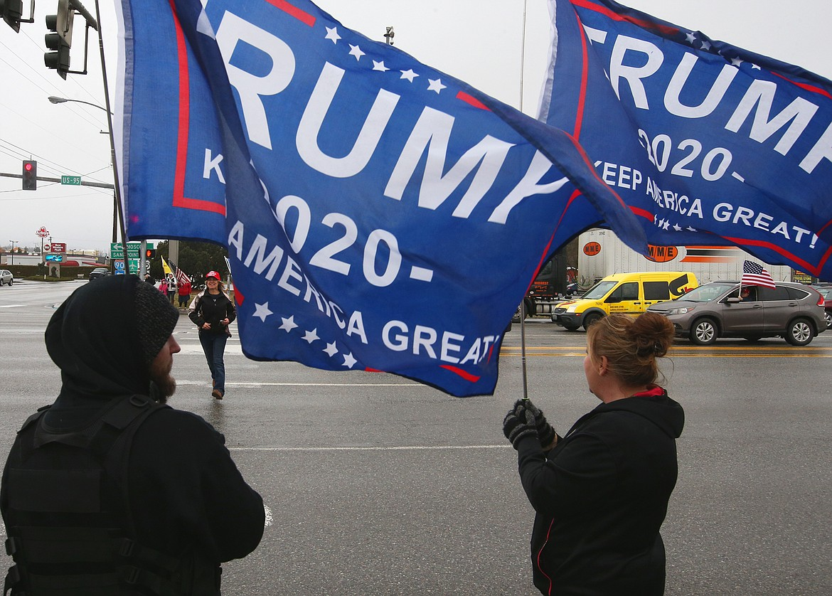 Austin Brady and Tammy Brady hold Trump banners on Wednesday.