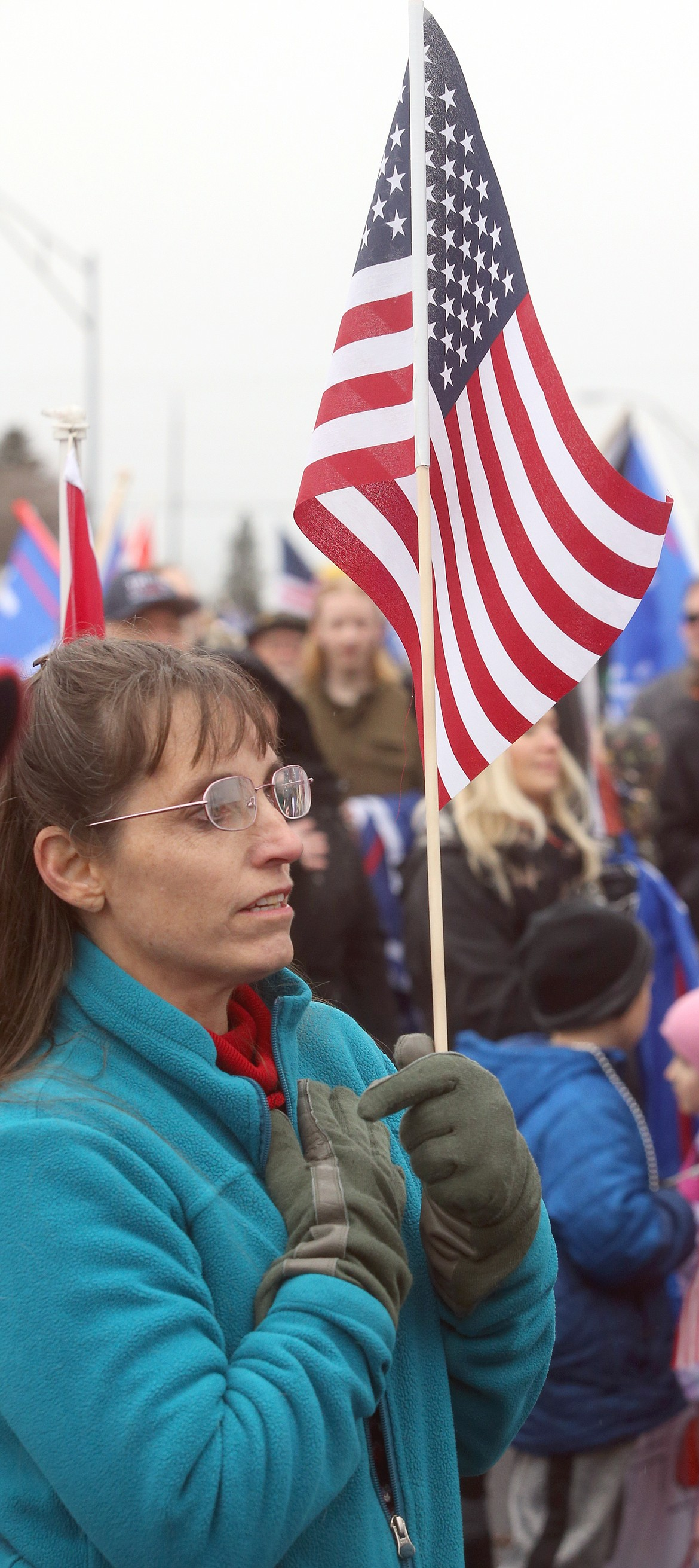 A woman holds her hand to her chest during the Pledge of Allegiance during the rally on Wednesday.