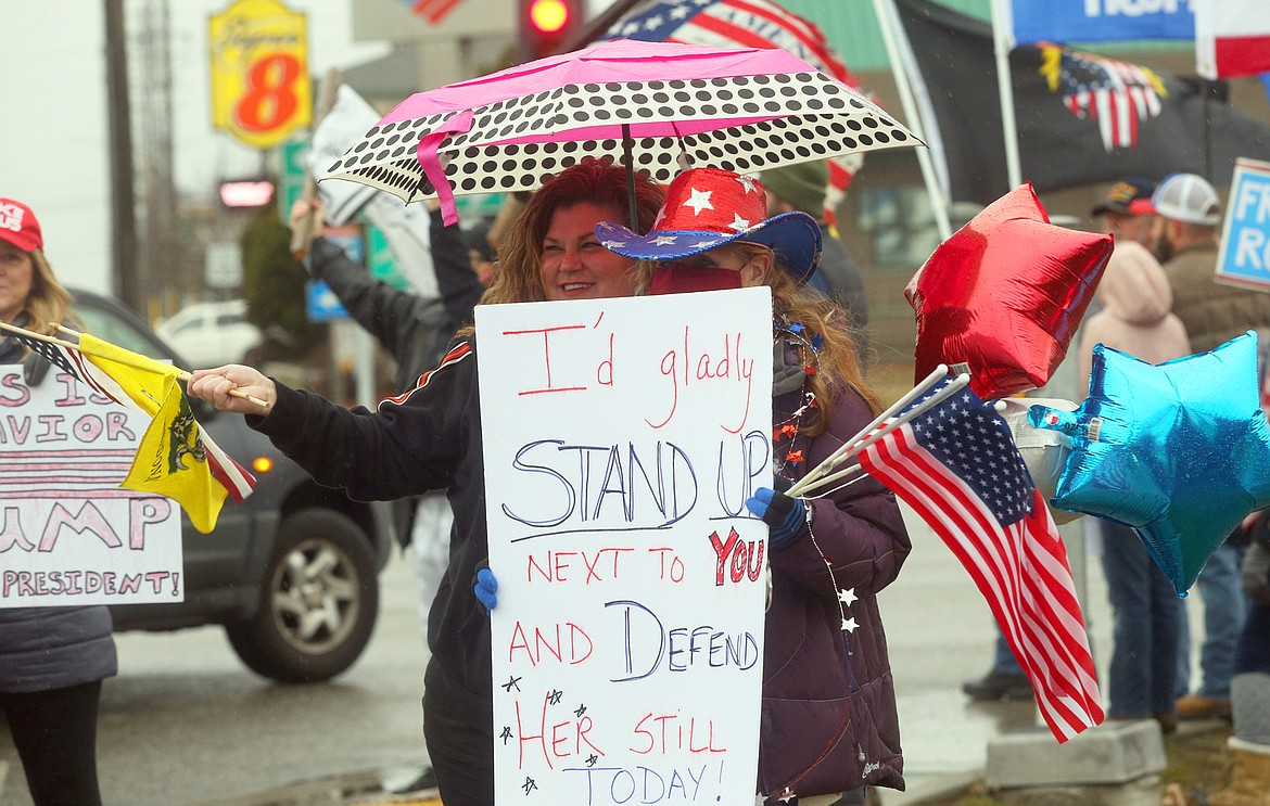 Lori Green, left, and Patty Stanfield, hold flags and balloons as they huddle under an umbrella and wave to passersby during Wednesday' pro-Trump rally in Coeur d'Alene.