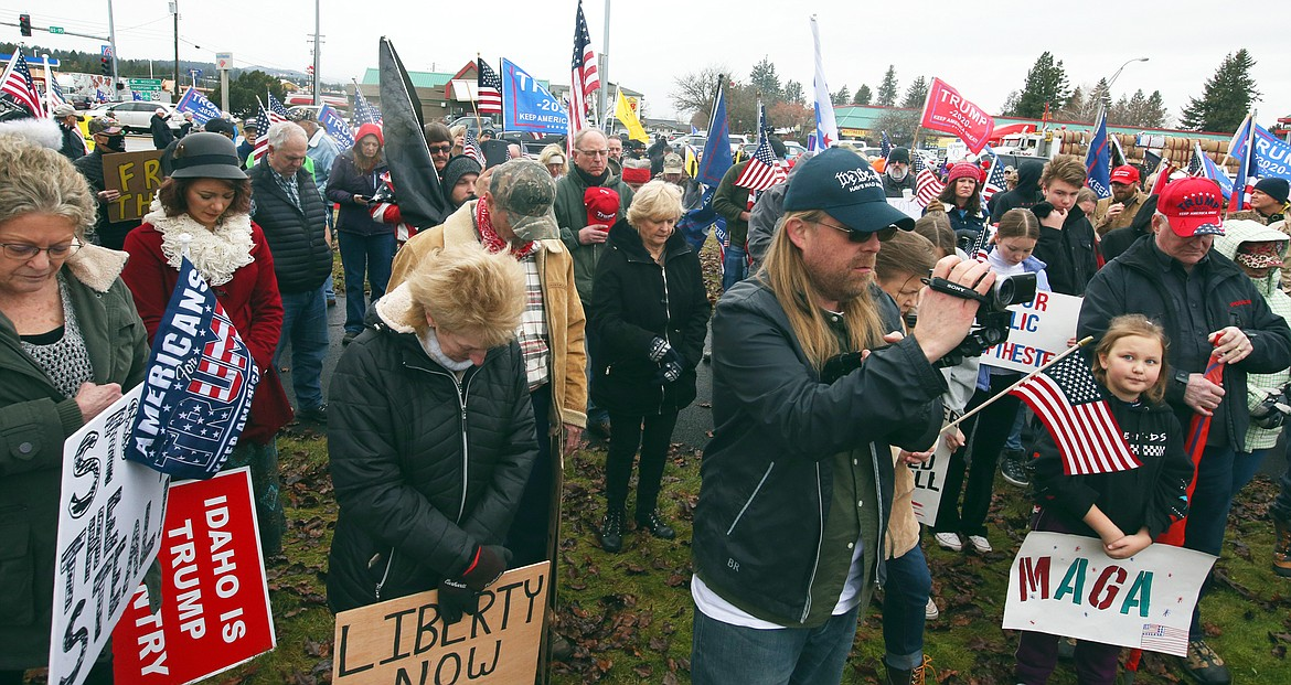 Some of the crowd at Wednesday's rally in Coeur d'Alene bows their heads in prayer.
