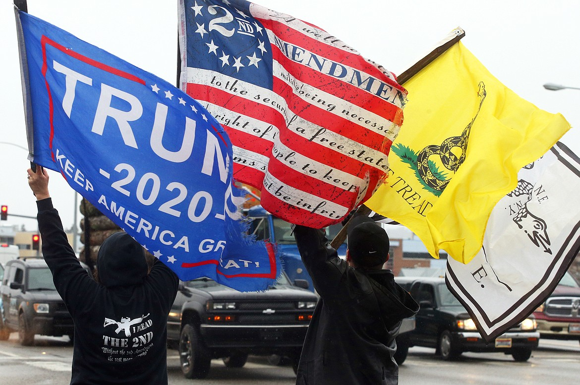 A few of the protesters at Wednesday's rally wave flag at the corner of U.S. 95 and Appleway Ave.