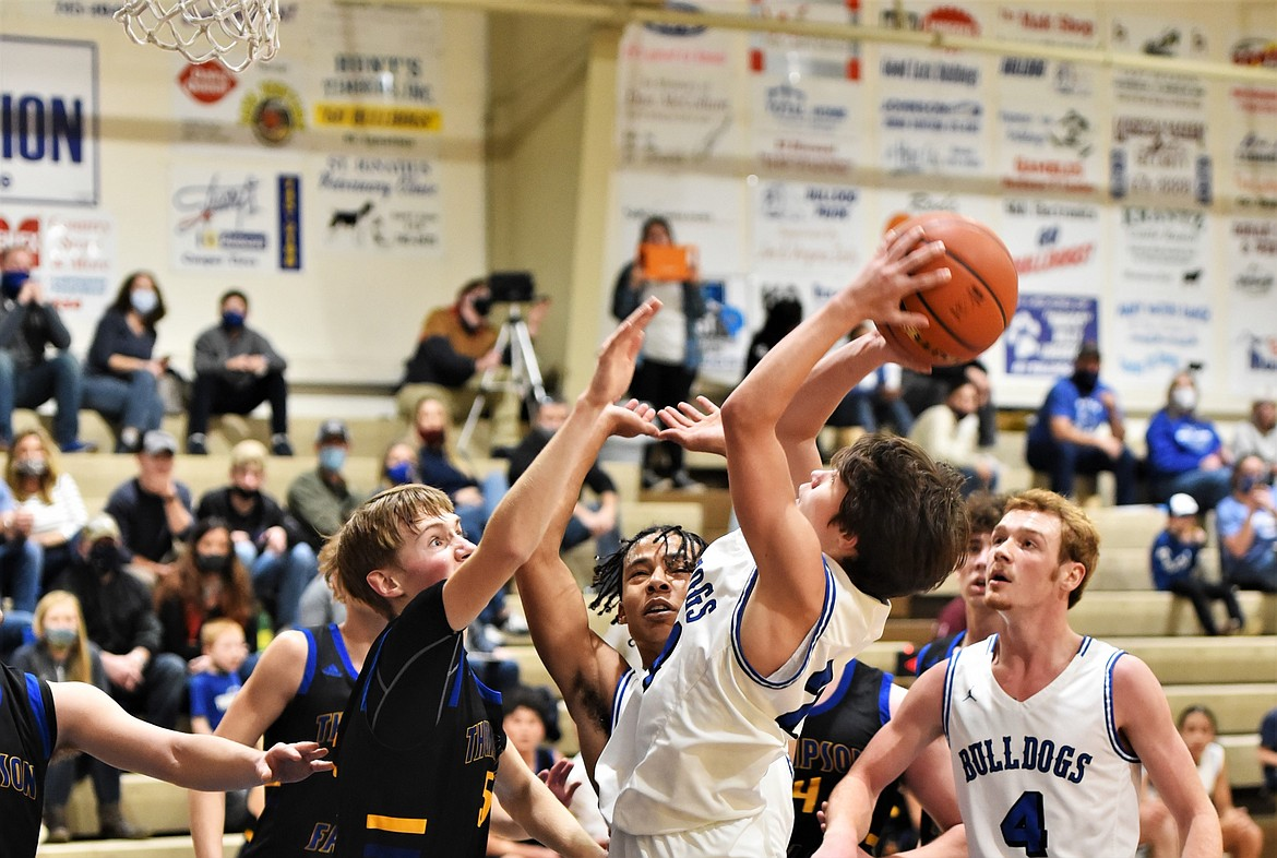 Zoran LaFrombois puts up a shot in a crowd, as Thompson Falls' Justin Morgan defends, in front of Bulldogs Layne Spidel (4) and Javon Bolen. (Scot Heisel/Lake County Leader)