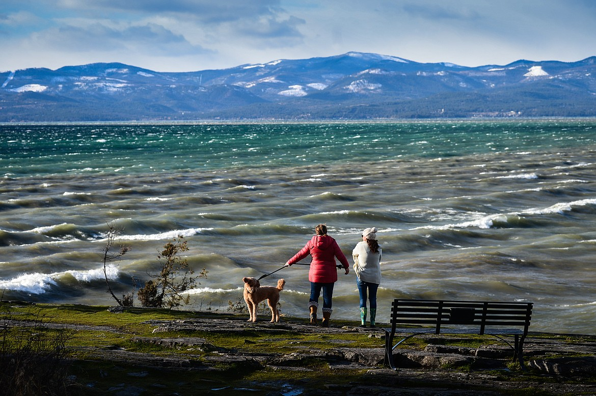 Beth Woods, left, and Shannon Amaral, with their dogs Murphy and Madison, take pictures of the waves rolling across Flathead Lake at Wayfarers State Park in Bigfork on Wednesday, Jan. 13. (Casey Kreider/Daily Inter Lake)