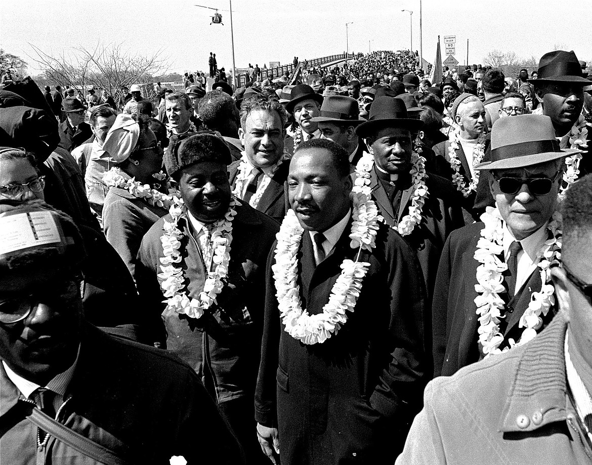 """In this March 21, 1965 file photo, Martin Luther King, Jr. and his civil rights marchers cross the Edmund Pettus Bridge in Selma, Ala., heading for the capitol, Montgomery, during a five day, 50 mile walk to protest voting laws. The annual celebration of the Martin Luther King Jr. holiday in his hometown in Atlanta is calling for renewed dedication to nonviolence following a turbulent year. The slain civil rights leader's daughter, the Rev. Bernice King, said in an online church service Monday, Jan. 18, 2021, that physical violence and hateful speech are """"out of control"""" in the aftermath of a divisive election followed by a deadly siege on the U.S. Capitol in Washington by supporters of President Donald Trump."""