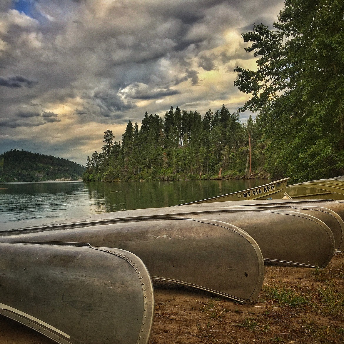 Canoes rest on the shore of Flathead Lake
