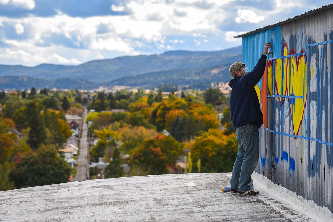 Artist Thomas Valencia spray-paints a colorful train to cover up graffiti atop the grain silos at the former CHS site in Kalispell on Sunday, Oct. 11. (Casey Kreider/Daily Inter Lake)