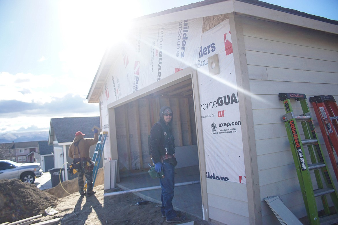 Victor Gonzales (front) and Gabriel Cardillo put up the siding on an Orchard View home.