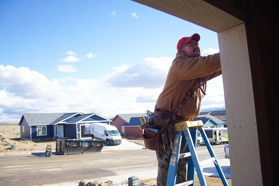 Gabriel Cardillo puts up siding on an Orchard View home.