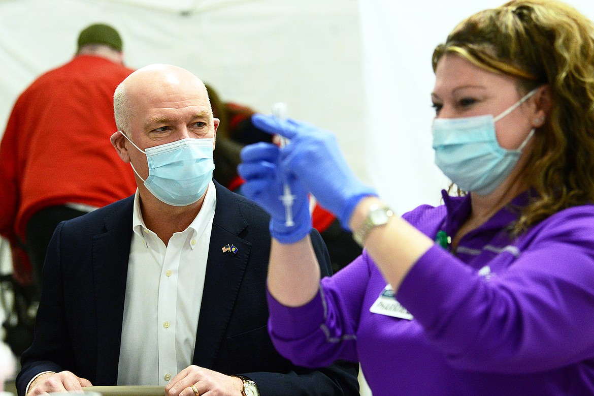 Gov. Greg Gianforte speaks with Melissa Pfeifle, a pharmacist with Kalispell Regional Healthcare, as she prepares COVID-19 vaccines during a clinic at the Flathead County Fairgrounds in Kalispell on Friday, Feb. 12. (Casey Kreider/Daily Inter Lake)