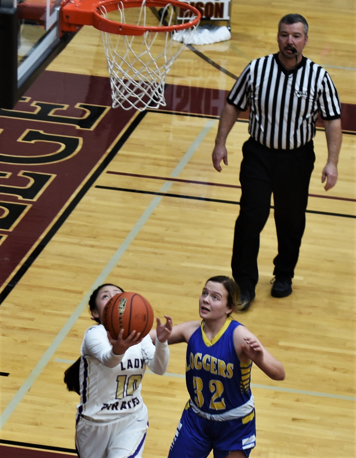 Jaivin Bad Bear puts up a reverse layup Saturday as Libby's Kinzee Boehmler defends. (Scot Heisel/Lake County Leader)