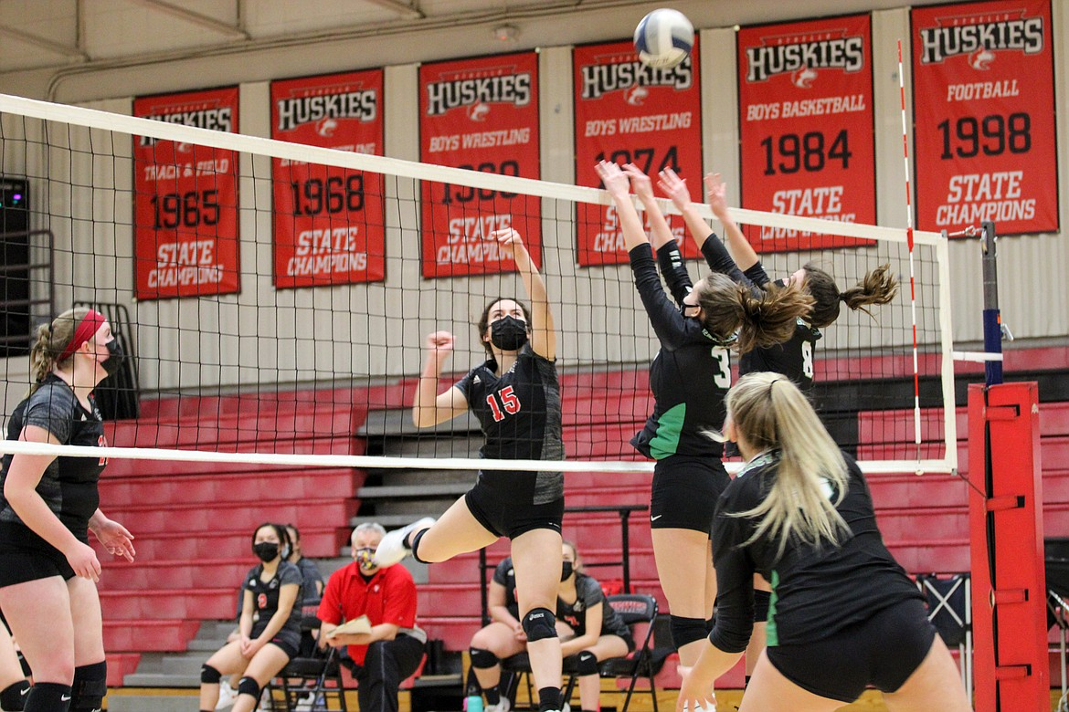 Othello's Natalie Martinez puts the ball just over the East Valley (Spokane) defenders during the first set of the Huskies' 3-0 win over the Knights on Thursday night at Othello High School.