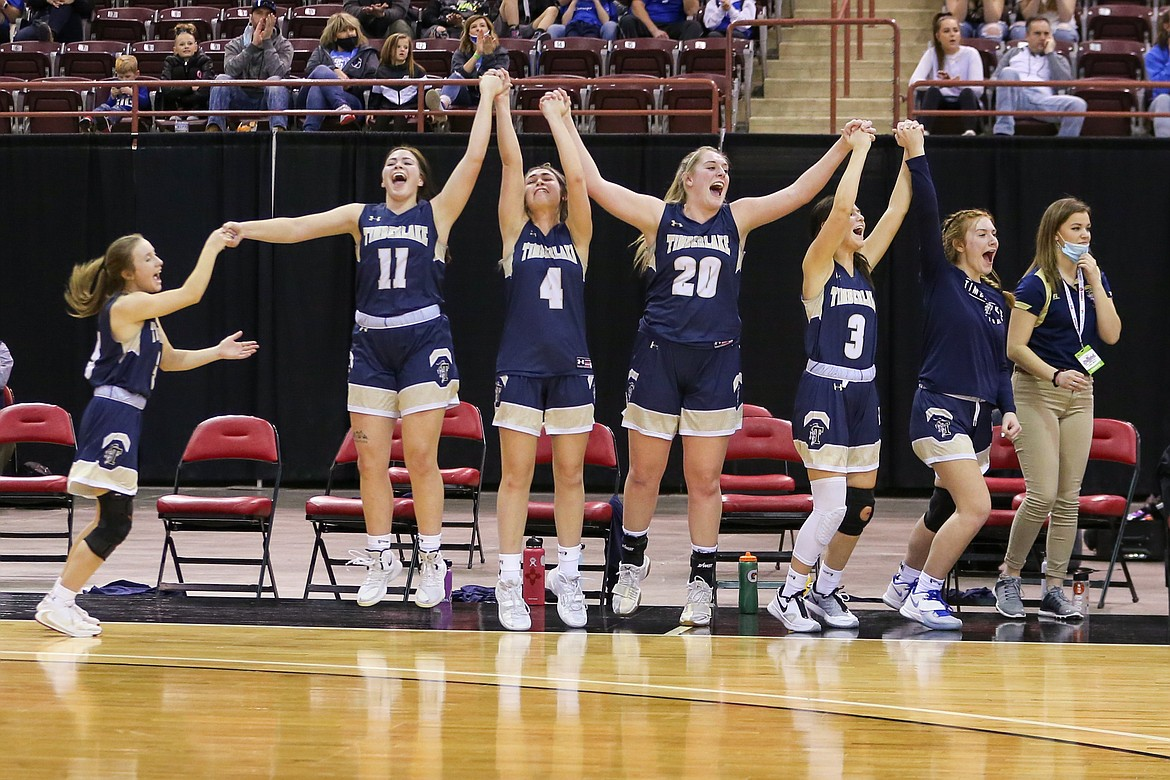 JASON DUCHOW PHOTOGRAPHY From left, Ciara Soumas, starters Bernie Carhart (11), McKennah Kronenberg (4), Brooke Jessen (20) and Olivia Hammond (3), reserve Morgan Dickinson and assistant coach Jacquelyn Mallet of Timberlake celebrate in the closing seconds as the Tigers won their second straight state 3A girls basketball championship, beating Sugar-Salem on Saturday at the Ford Idaho Center in Nampa.