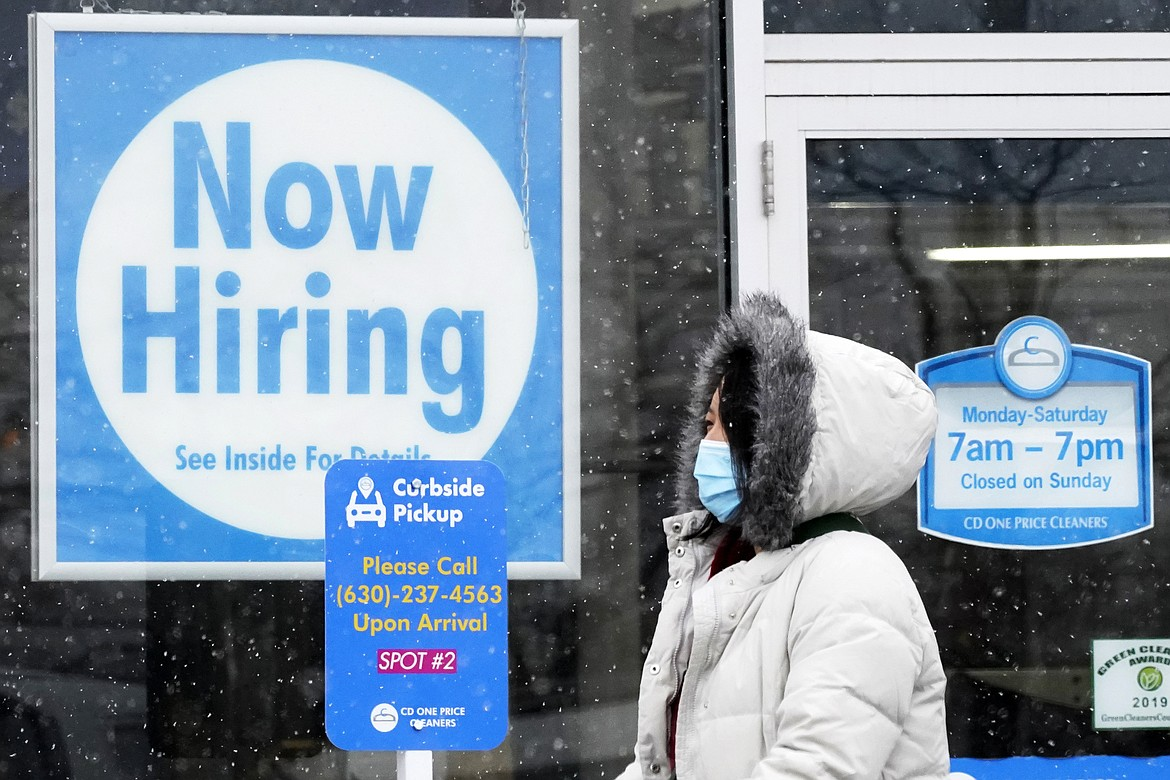 """In this Feb. 6, 2021, file photo, a woman walks past a """"Now Hiring"""" sign displayed at a CD One Price Cleaners in Schaumburg, Ill. U.S. employers added a surprisingly robust 379,000 jobs in February in a sign the economy is strengthening as virus cases drop, vaccinations ramp up, Americans spend more and states ease business restrictions."""