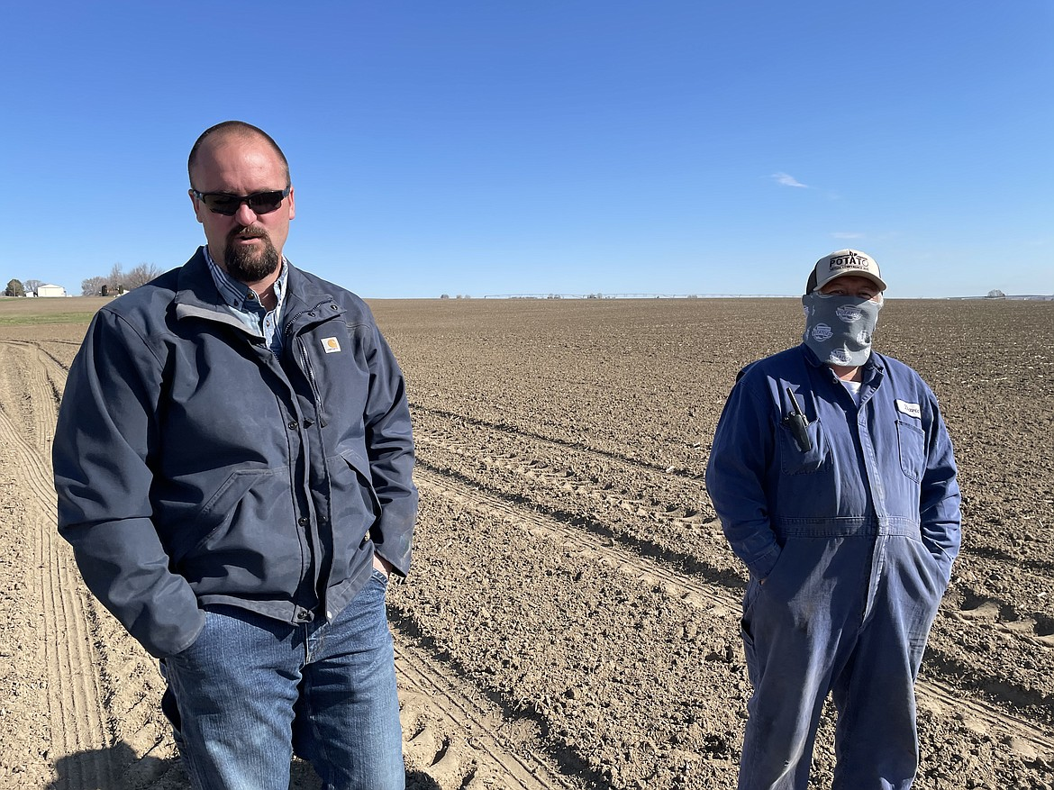 Grant Morris (left) and David Razo (right) oversee the planting of seed potatoes in one of the fields cultivated by Schneider Farms of Pasco. Razo, who has worked for Schneider Farms for 7 years, regularly checks to make sure the potatoes are planted at the right depth and the right spacing in order to ensure that they will grow properly.