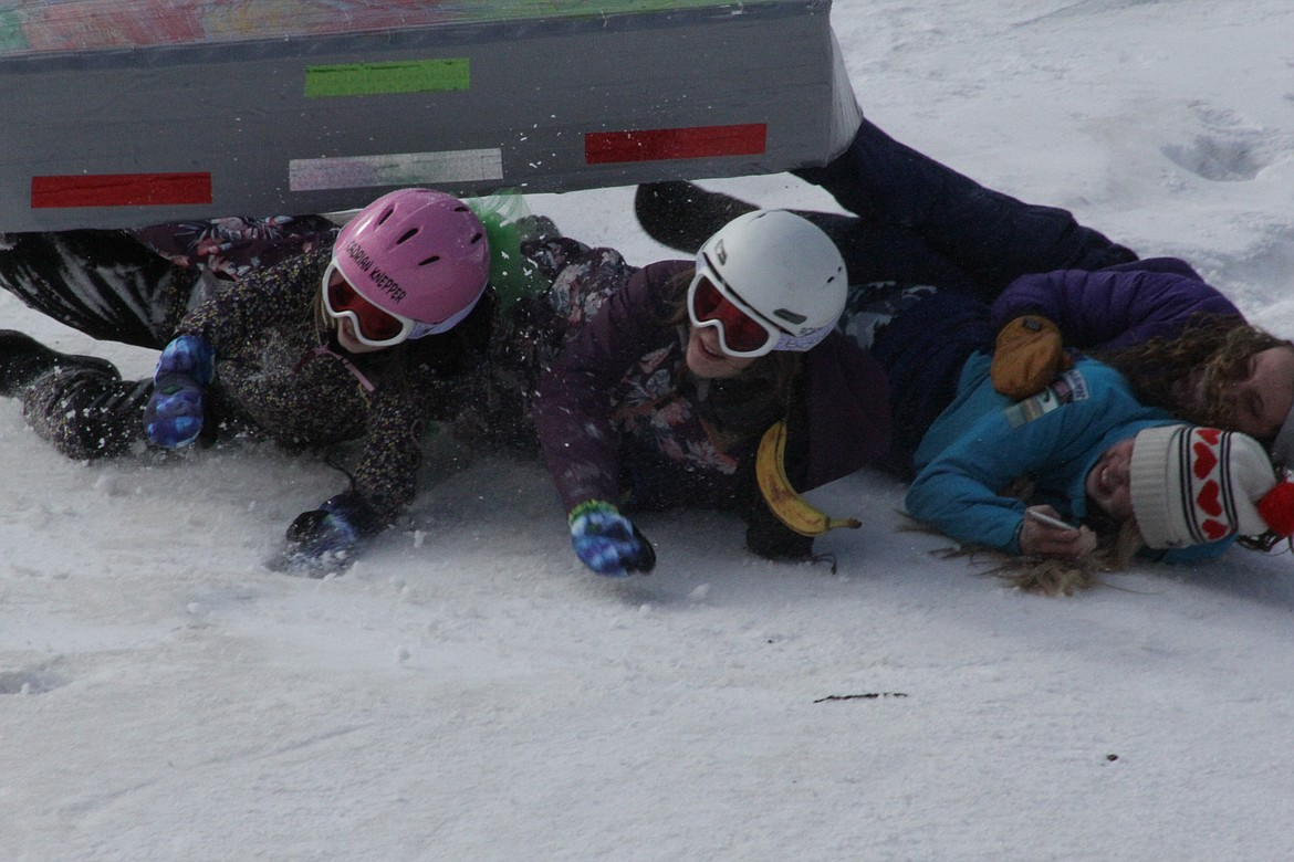 Joecy, Makia, Xadrian and Annemarie wipe out during a toboggan ride Tuesday morning at Schweitzer.