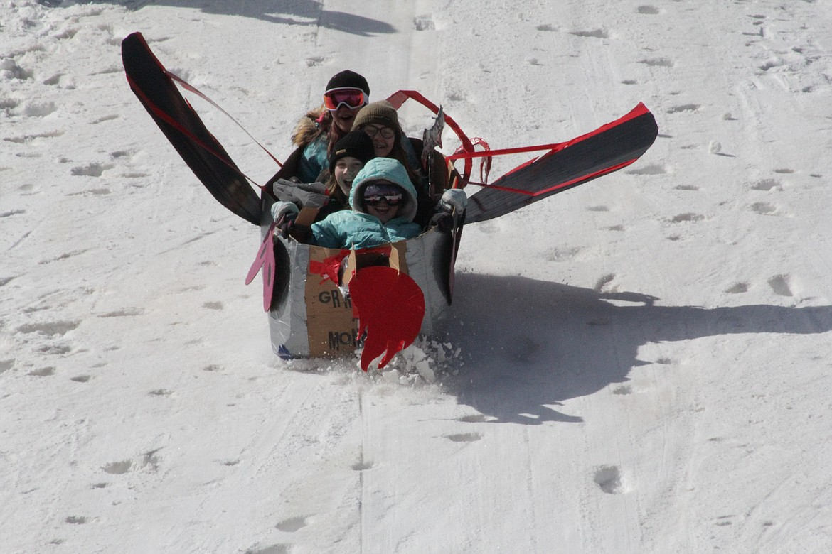 """Elka, Rowin and Lia and another student at the Homeschool Academy slide down the hill in their """"monster""""-themed toboggan."""