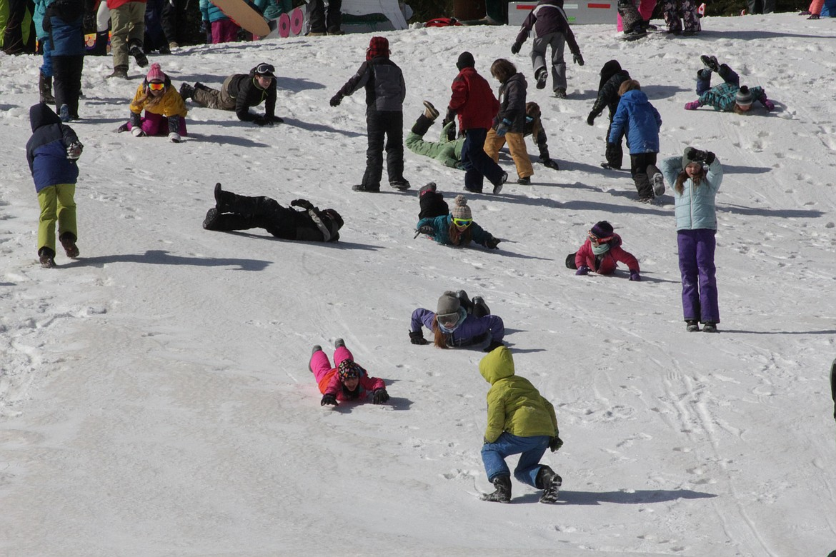 Children slide and roll down the hill while waiting for their turn on the toboggans.