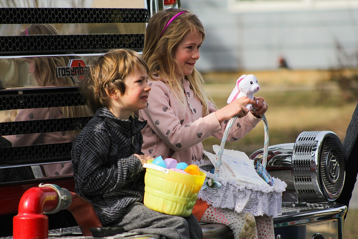 Children pose for a photo on the firetruck following the Easter egg hunt.