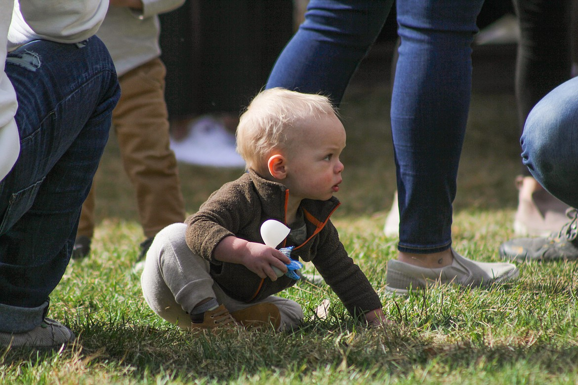 A child opens one of his plastic eggs filled with candy Saturday at the egg hunt.