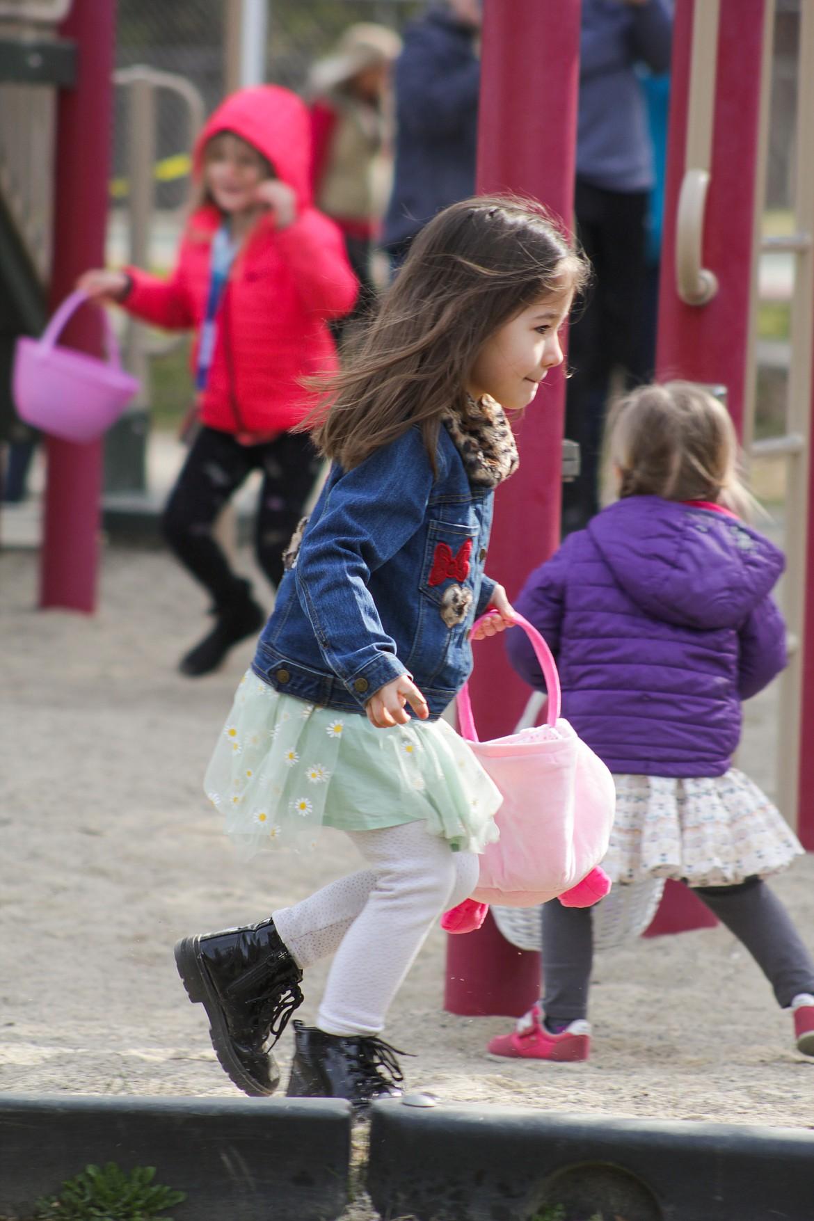 A girl runs to pick up an egg.