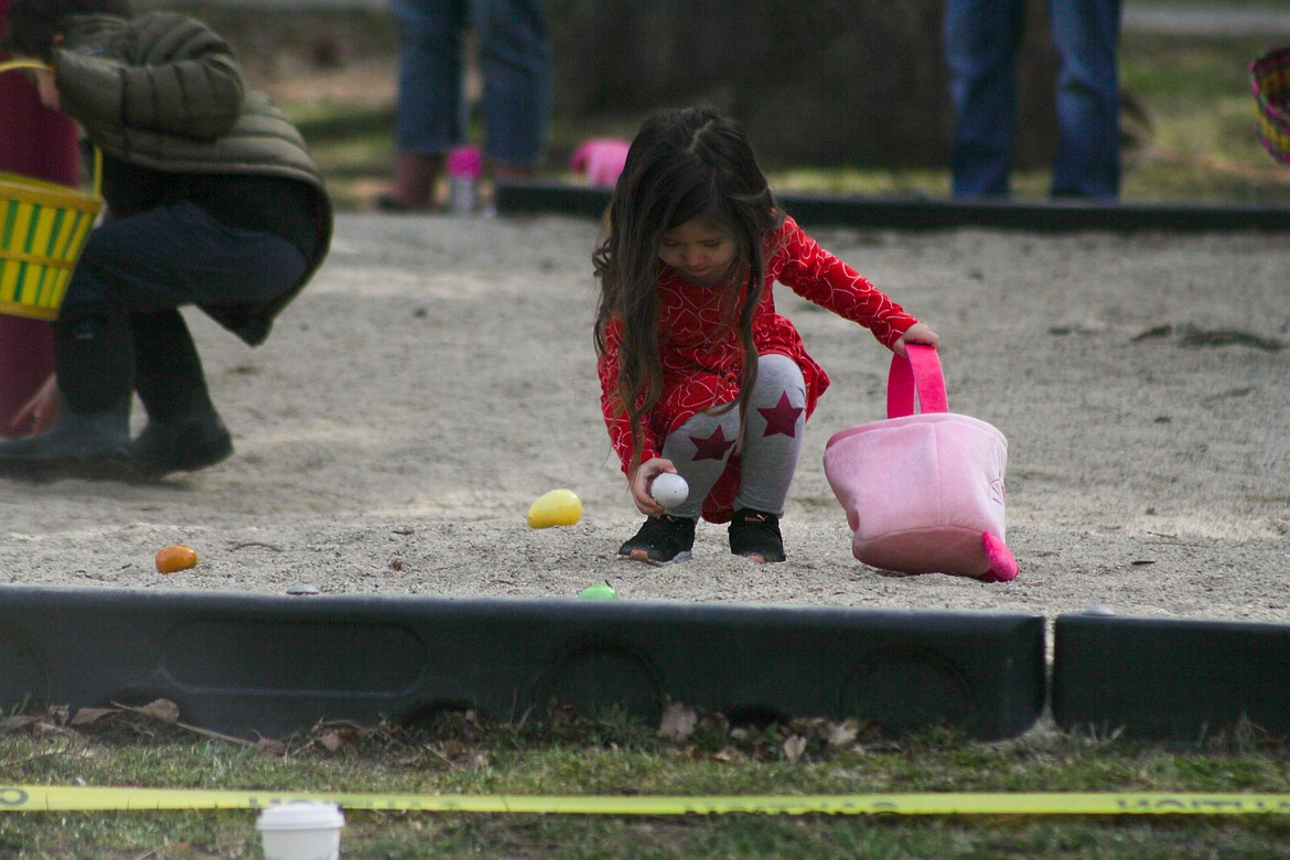 A girl bends down to pick up an egg at the Easter egg hunt Saturday at Lakeview Park.