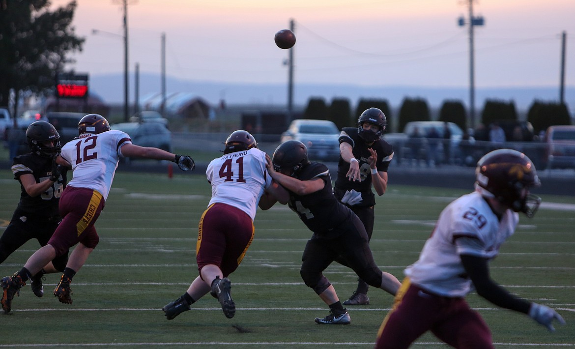 Royal's Caleb Christensen makes a pass downfield in the first half against Moses Lake on Friday night at RHS.