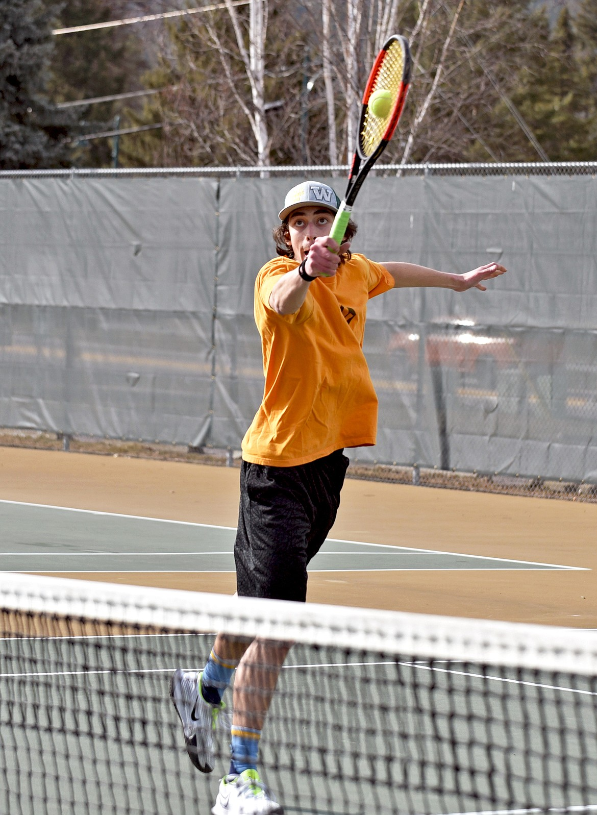 Whitefish senior Jayce Cripe hits a volley at the net during the high school boys tennis practice on Thursday. (Whitney England/Whitefish Pilot)
