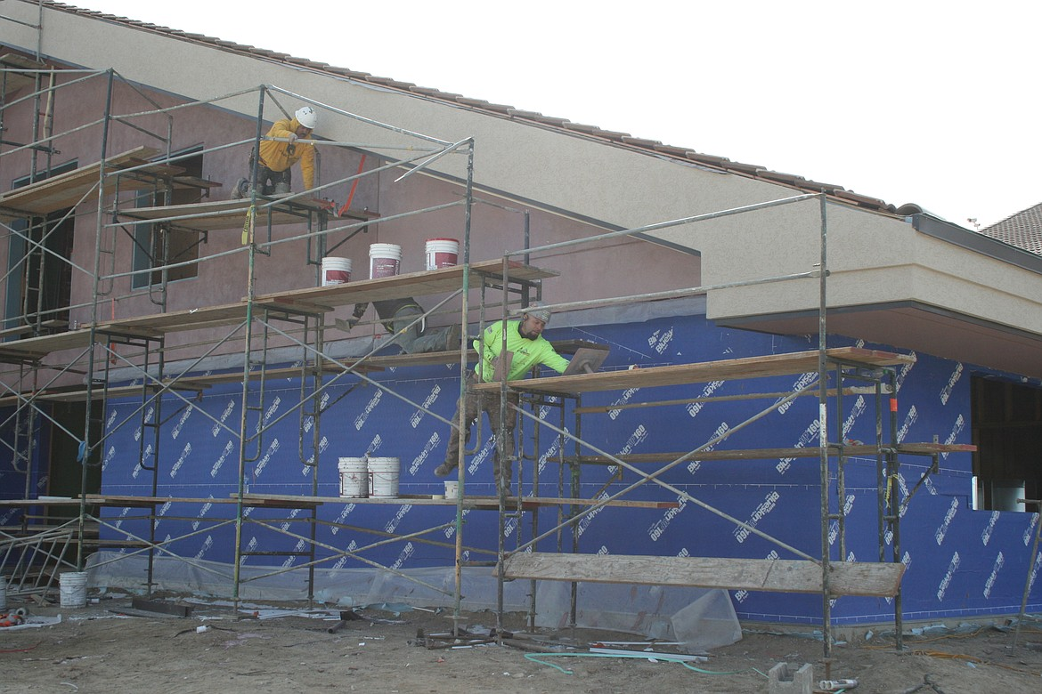 Construction workers Miguel Garcia (left) and Jairo Torres (right) apply stucco to the exterior of the addition at Royal Middle School Friday.