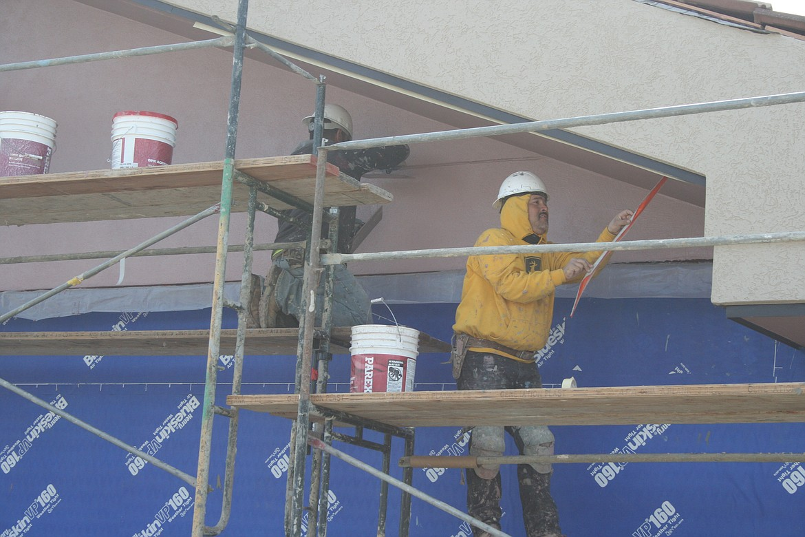 Miguel Garcia removes tape along the eaves of the addition to Royal Middle School Friday