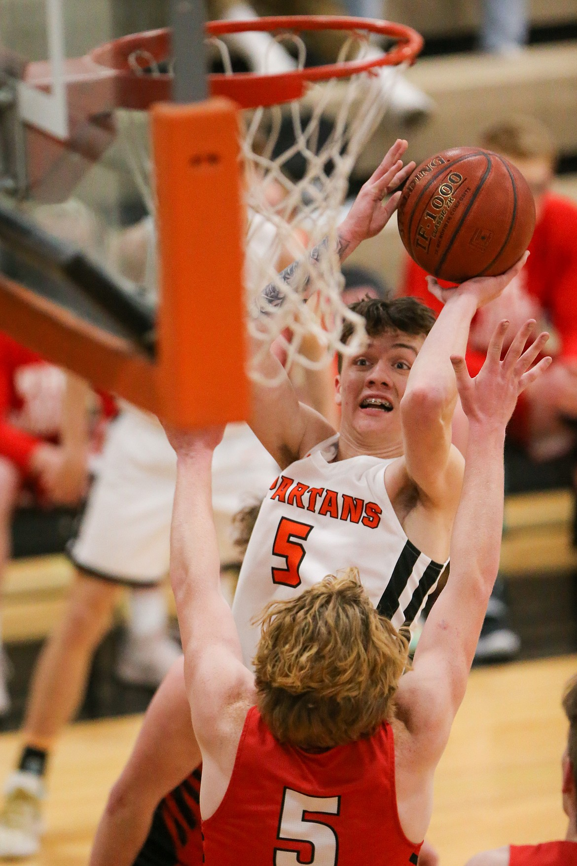 Priest River junior Trentyn Kreager attempts to knock down a shot over a Sandpoint defender during a home game this winter. Kreager was named a finalist for the 3A-1A boys basketball award.