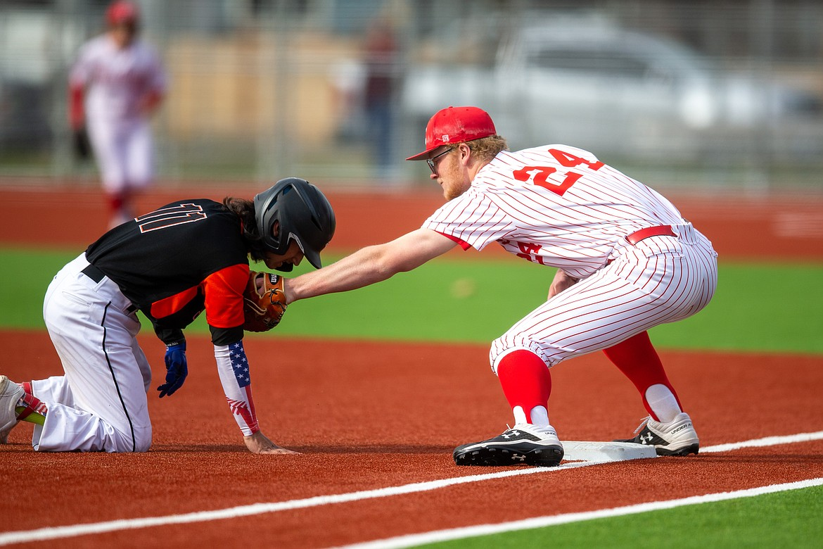 Sandpoint's Ethan Butler tags Priest River's Gavin Doster at first base last Thursday.
