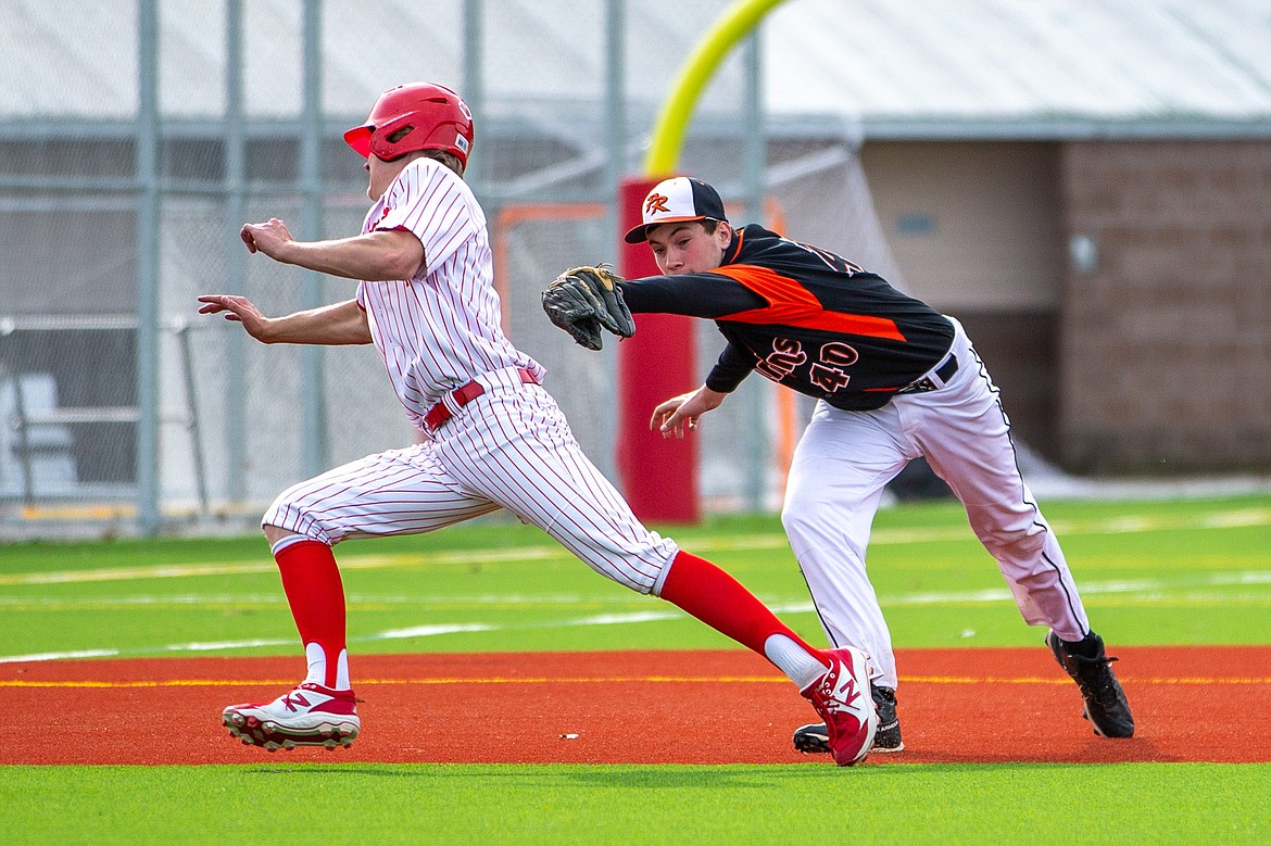 Sandpoint's Cody Newhart (left) avoids being tagged by Priest River's Landon Reynolds last Thursday.